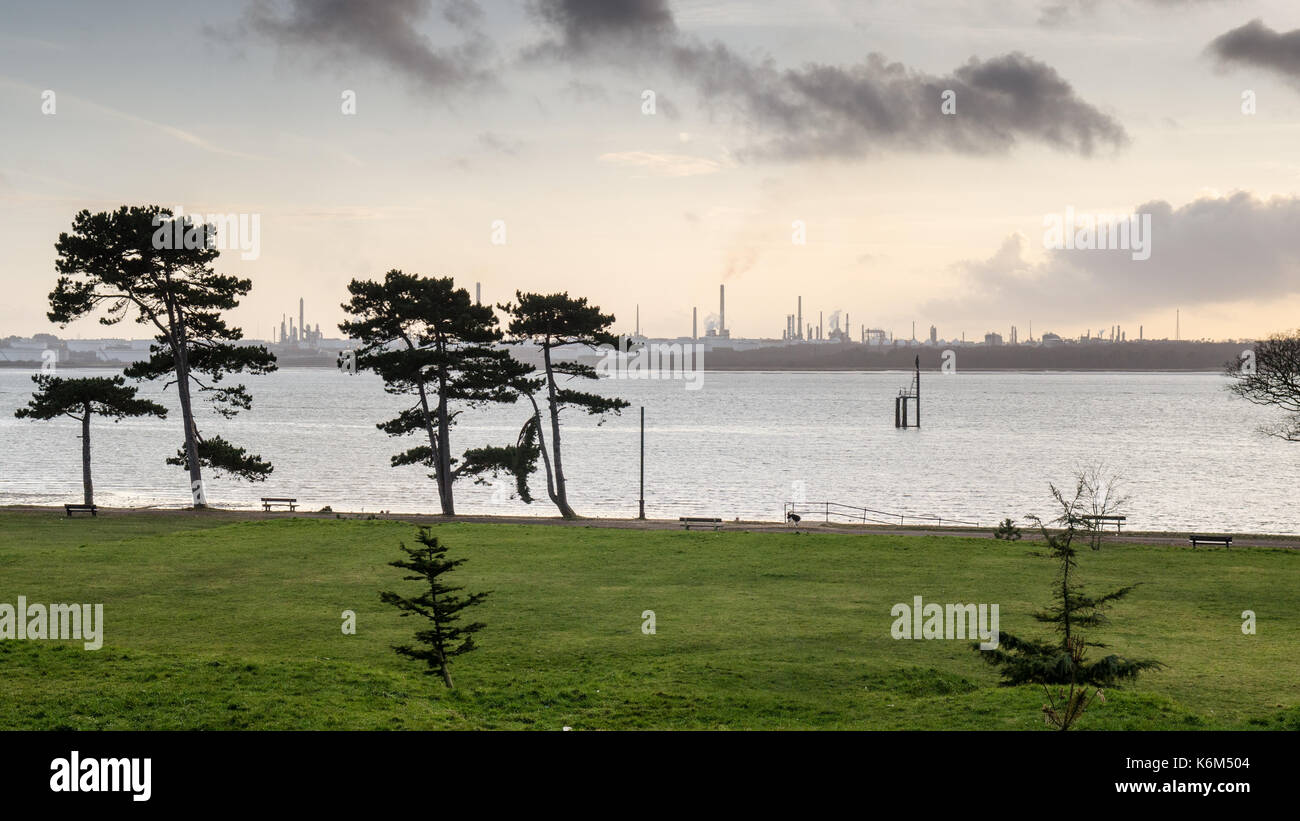 The sunset silhouettes the industrial towers of Esso's Fawley oil refinery and trees in Netley Country Park on the Stock Photo