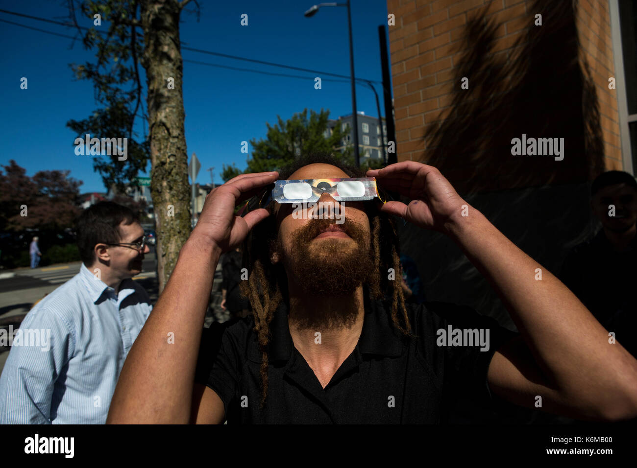 People gather on the streets of Seattle, WA, USA  to watch solar eclipse in August of 2017. - Stock Image