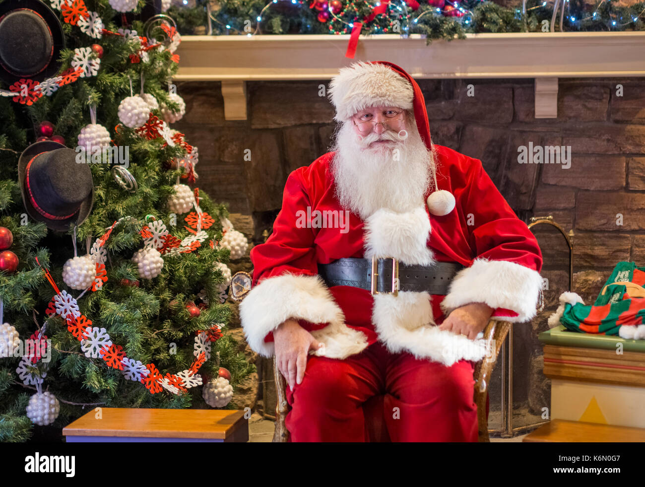 Sant waiting for kids to get their holiday shot clicked in an indoor setting. The backdrop shows a decorated Christmas tree with ornaments on it. - Stock Image