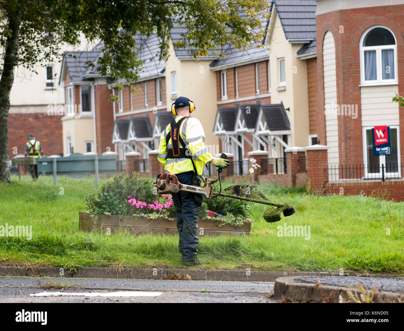 Worker in high vis jacket cutting grass with a petrol strimmer - Stock Image