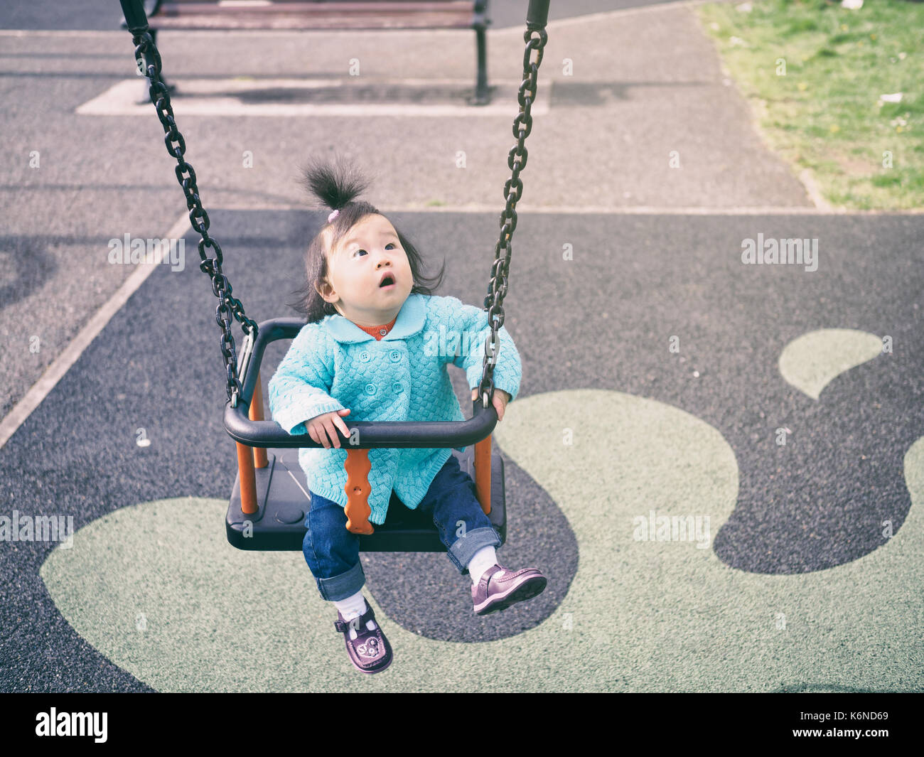 baby girl playing swing in the  playground Stock Photo
