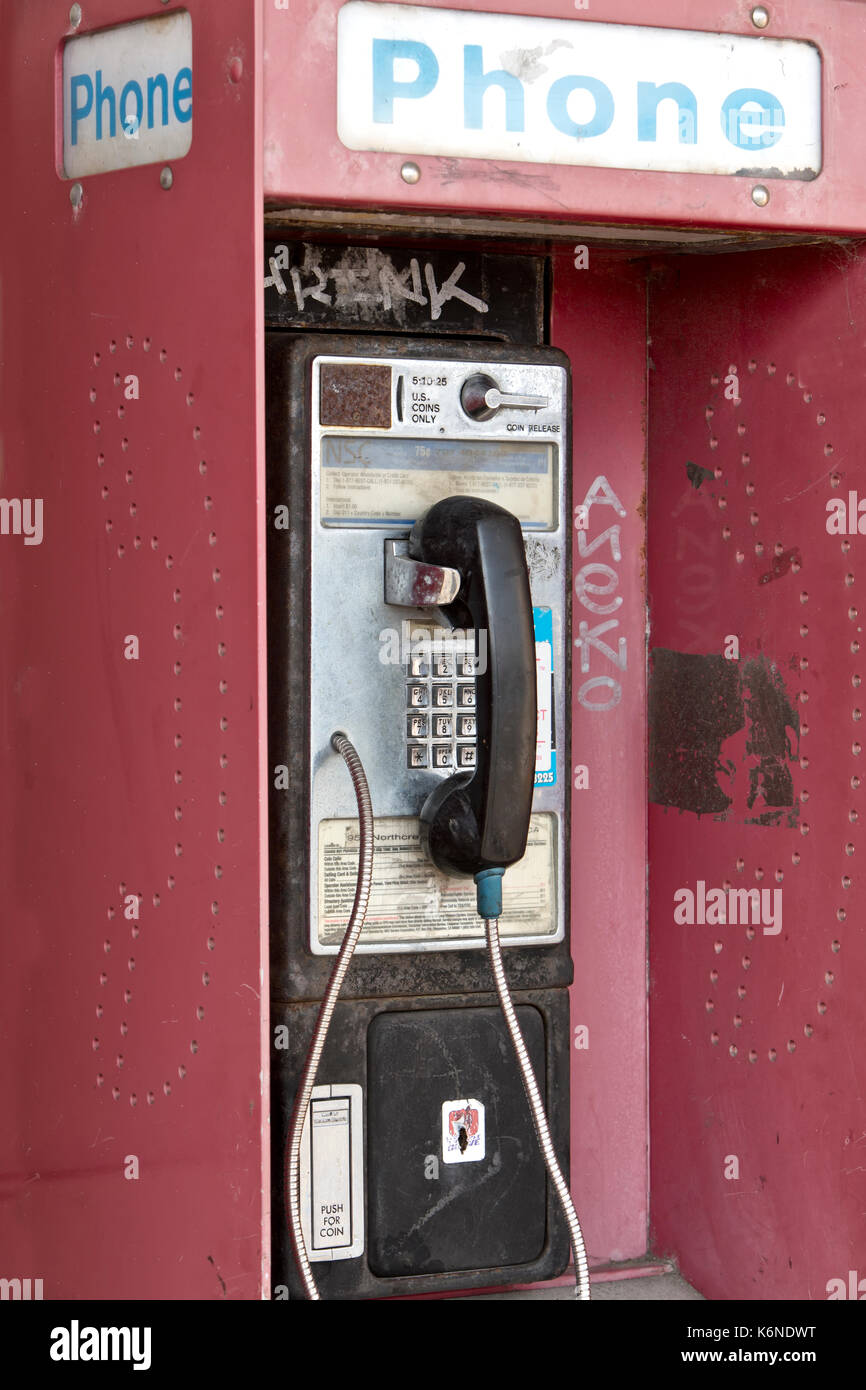 Abandoned 'Antique' coin operated public telephone with coin release slot, graffiti, old shopping center, California, United States. - Stock Image