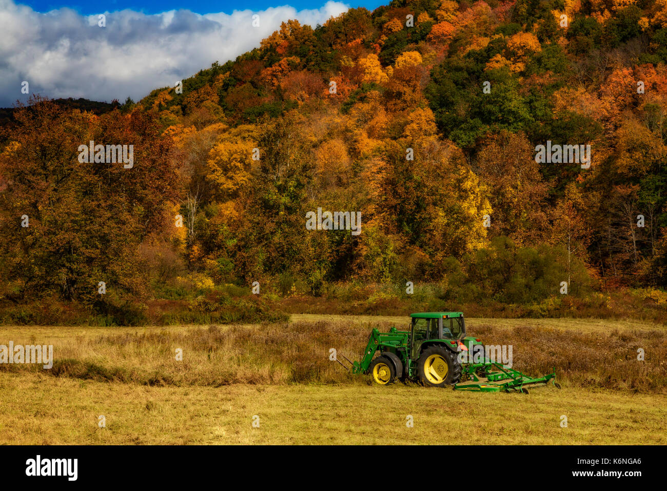 John Deere Tractor - Farmer works on the field with a John Deere 640 Tractor with a HX10 Rotary Cutter attachment in the back and bale spears in the f - Stock Image