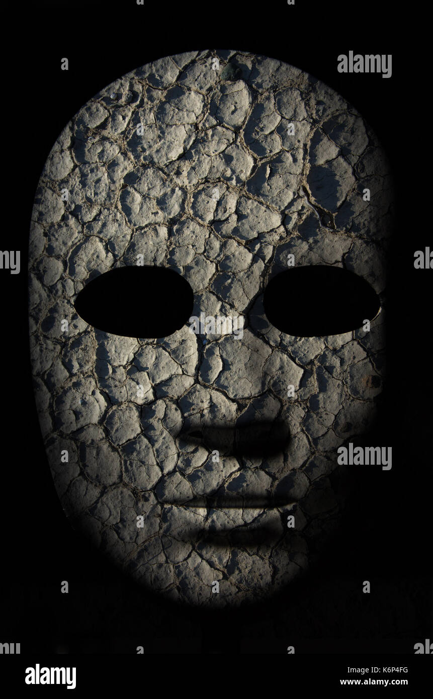 Textured mask with cracked rough wood  painted surface, neutral expression on dark background. - Stock Image