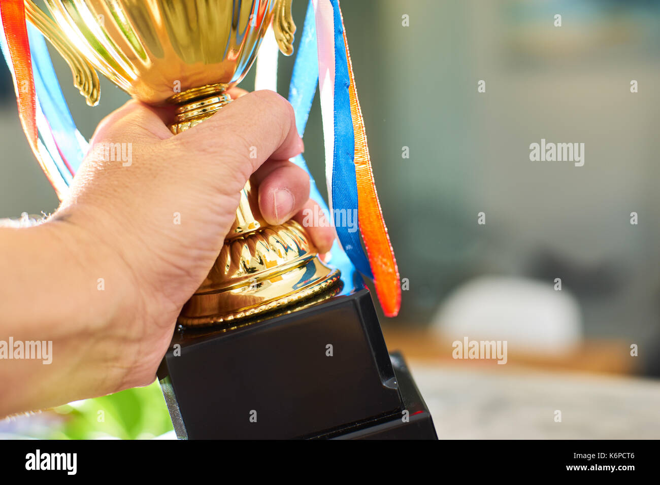 Young athlete holding up a gold trophy cup with space ready for your trophy design. - Stock Image
