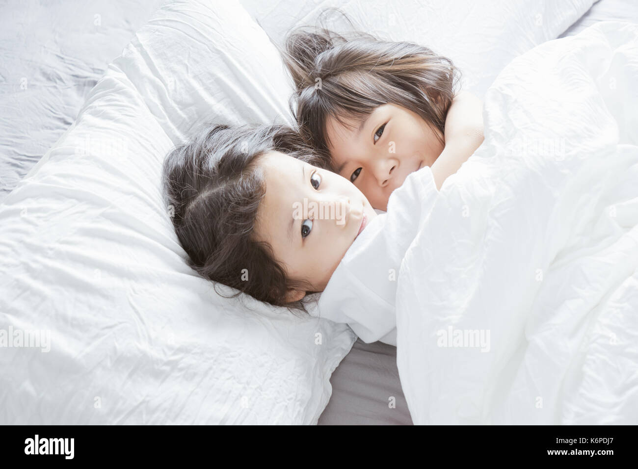 Two little asian chinese girl hug together and lying on the bed . - Stock Image
