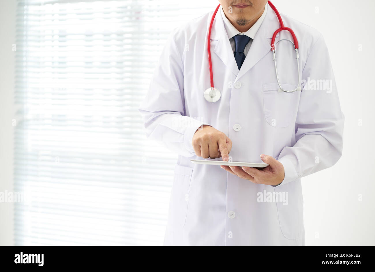 Unknown doctor posing using digital table with bright background, he is wearing a stethoscope . digital table in the office, he is wearing a stethosco - Stock Image