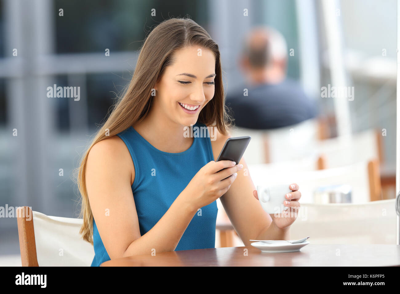 Single happy woman reading a phone message sitting in a bar - Stock Image