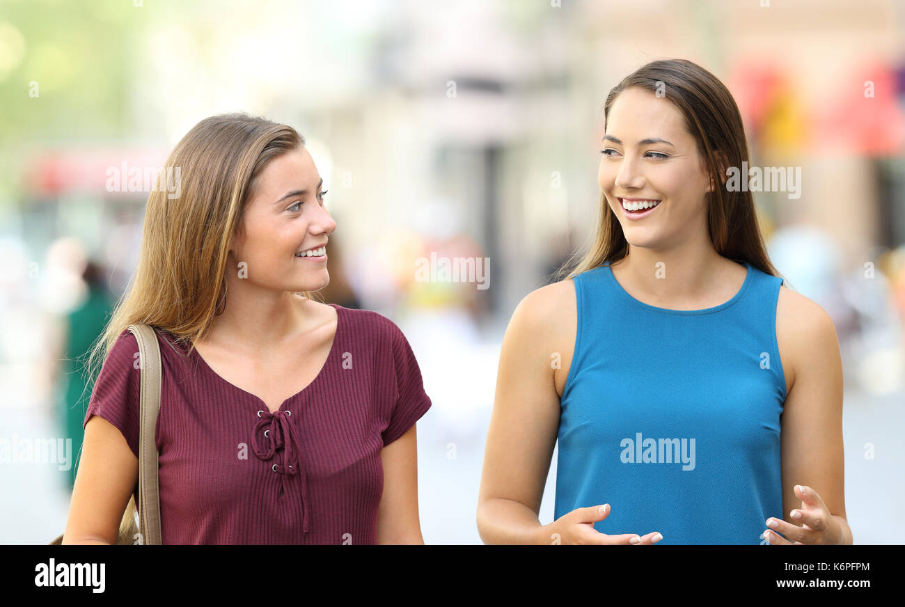 Two happy friends walking towards camera and talking on the street - Stock Image