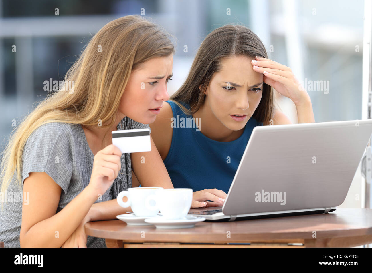Two worried women having problems buying on line with a laptop and credit card sitting in a bar - Stock Image