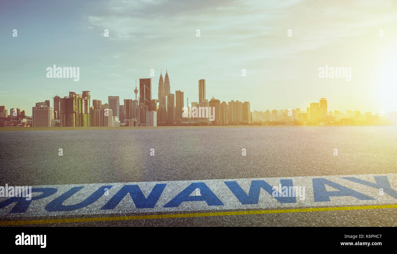 View of the empty asphalt road with runaway word and city skyline background . Evening scene . - Stock Image