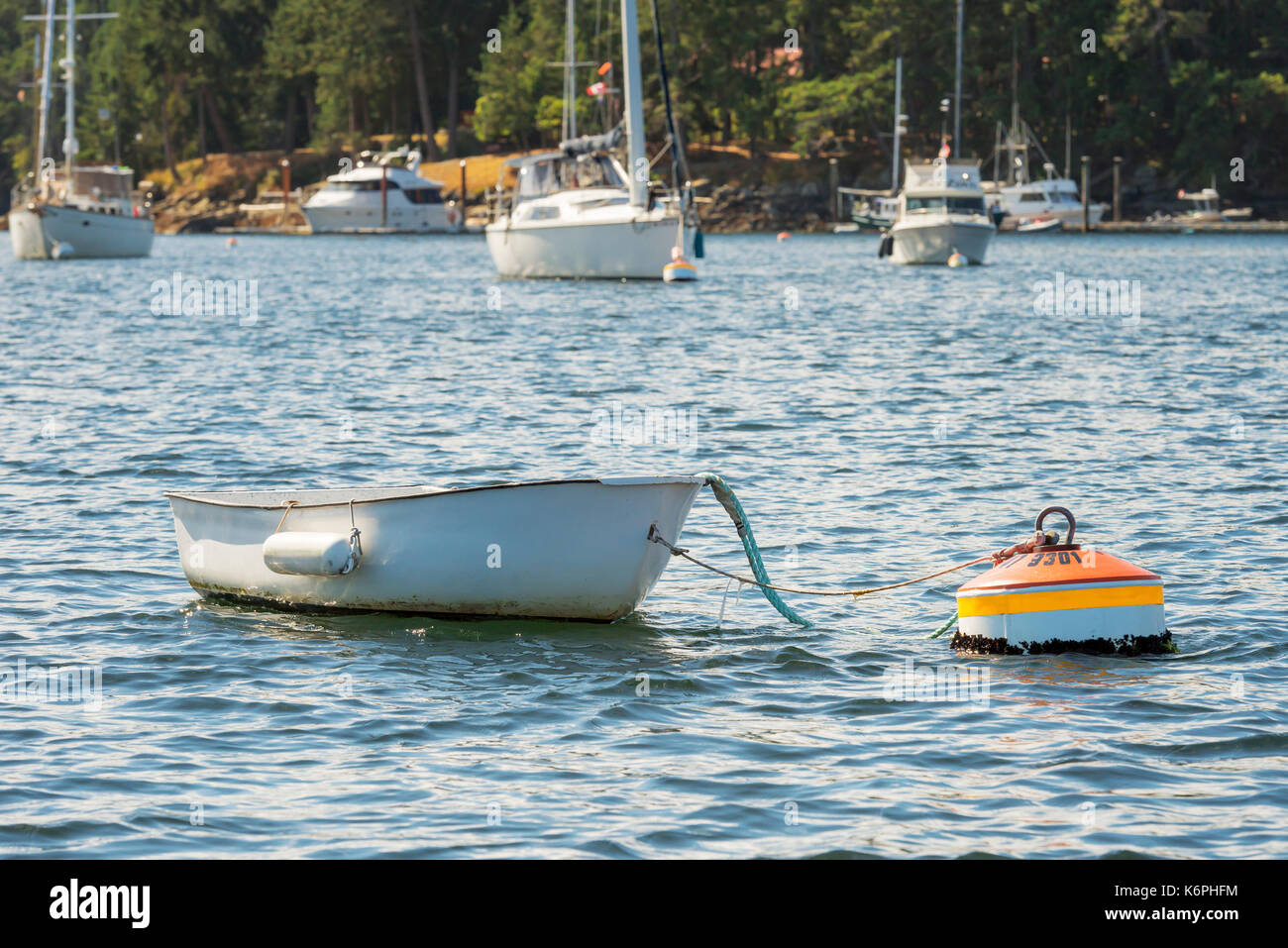 Small boat tied to a buoy - Stock Image