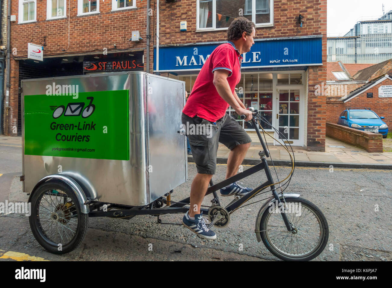 Green Link cycle courier on a tricycle with a large storage box for cargo providing a local emission free delivery in York - Stock Image