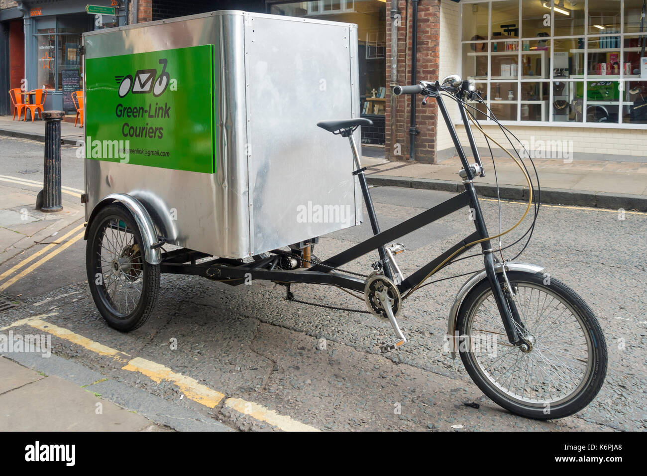 A parked Green Link tricycle with a large storage box for cargo providing a local emission free delivery in York - Stock Image