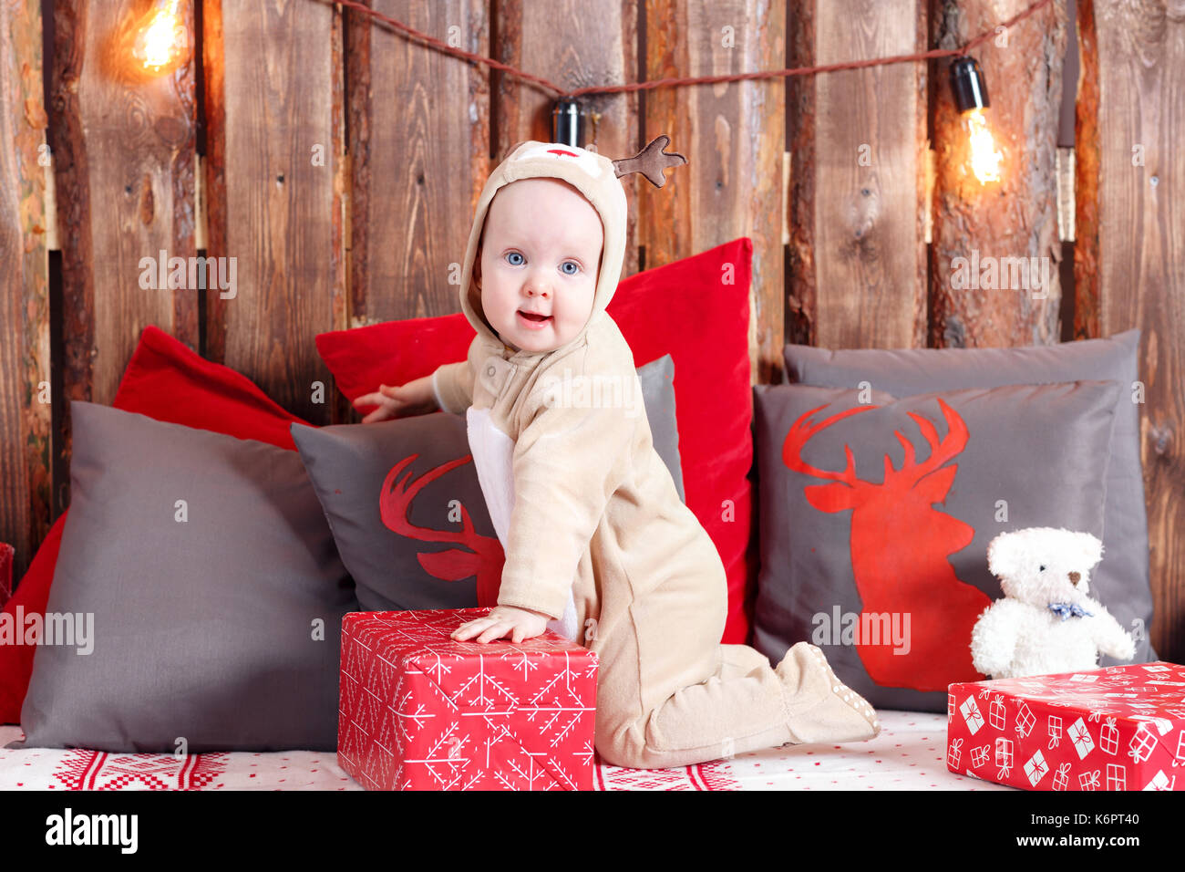 Christmas evening. Little girl sitting and unwraps gifts. coverall-reindeer costume - Stock Image