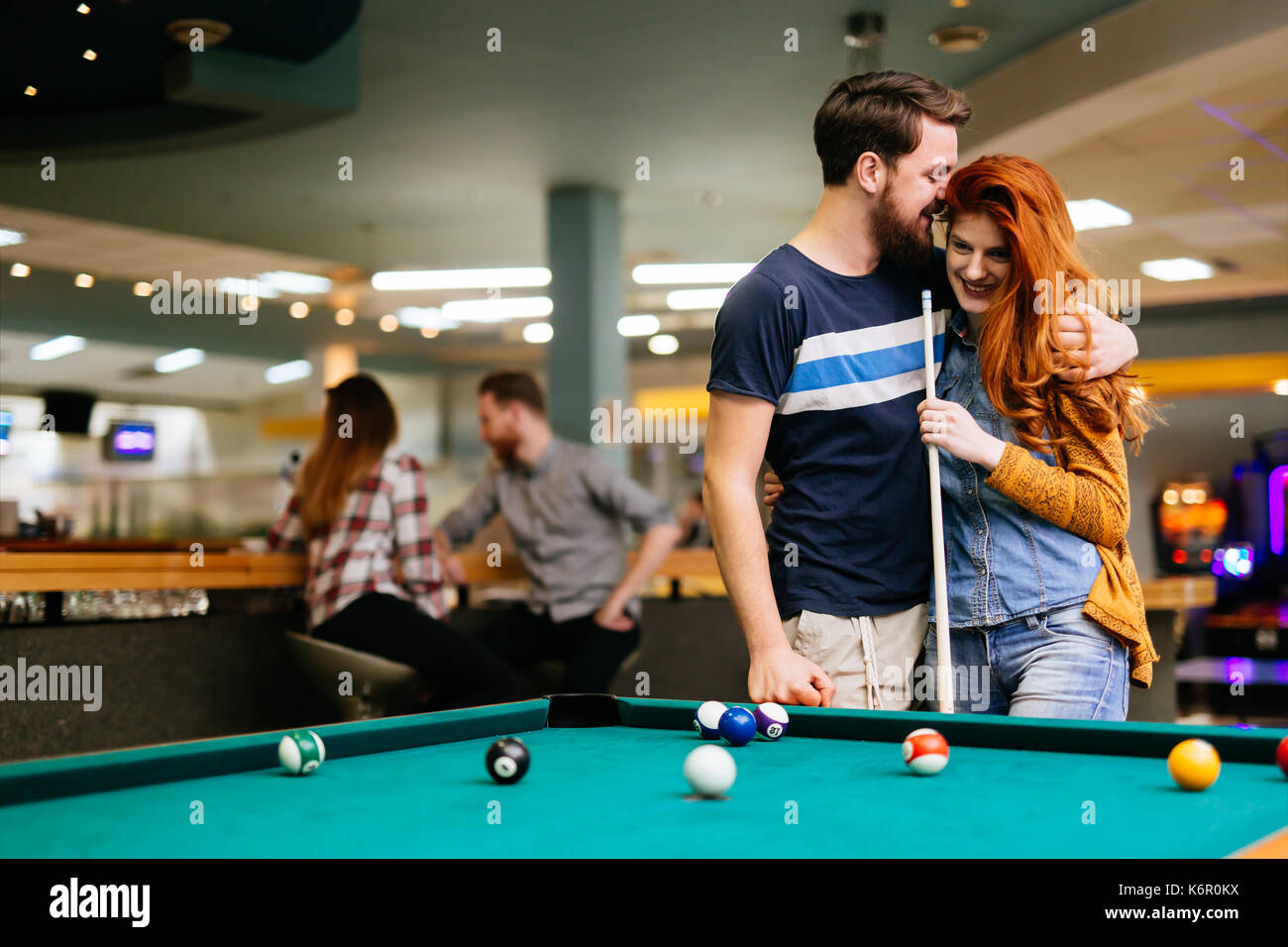 Couple spending time together by playing pool - Stock Image