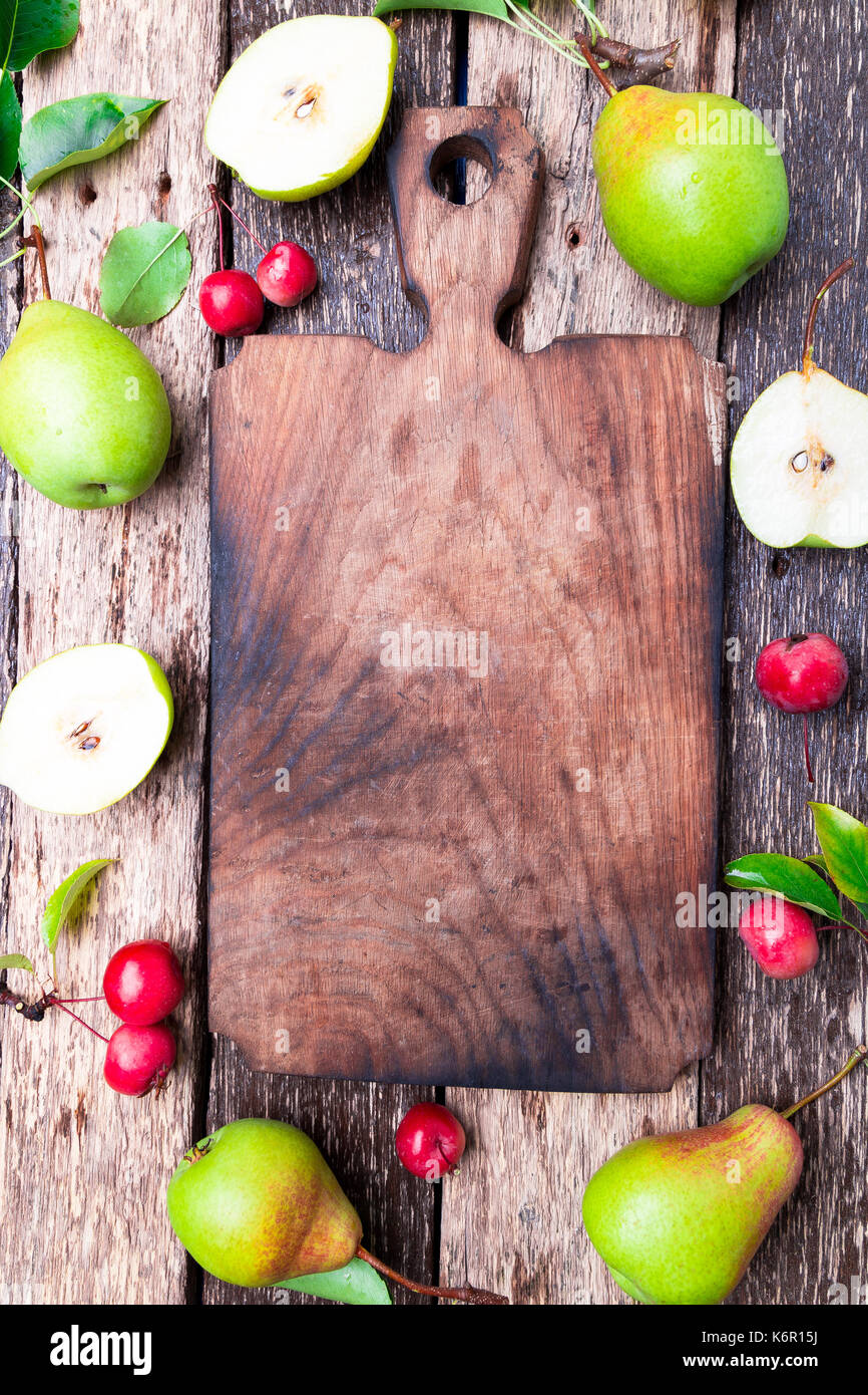 Pear and small apple around empty cutting board on wooden rustic background. Top view. Frame. Autumn harvest. Copy space - Stock Image