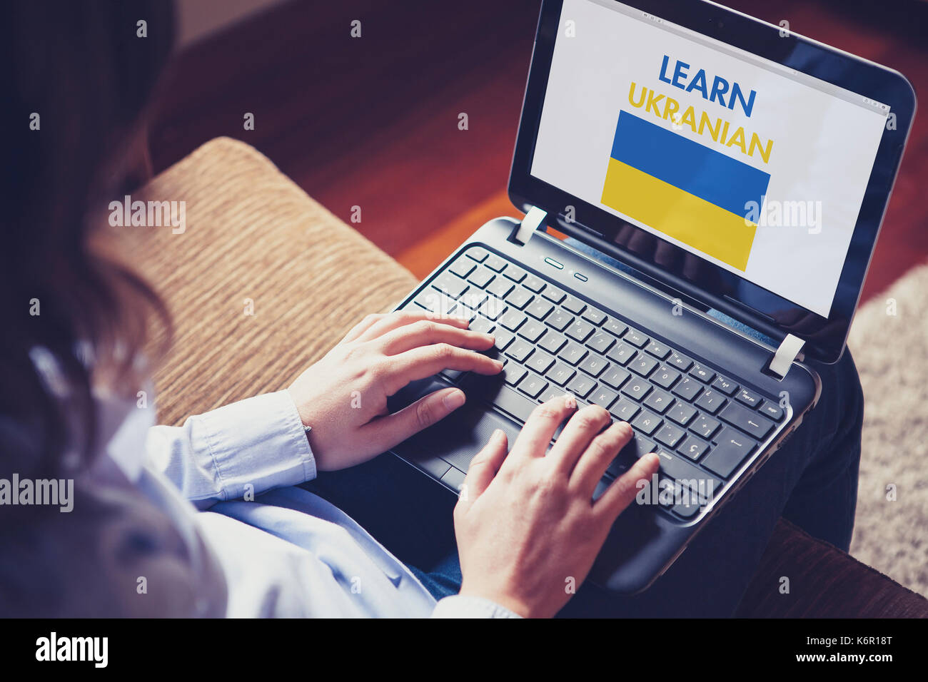 Woman using a laptop computer to learn Ukranian by internet - Stock Image