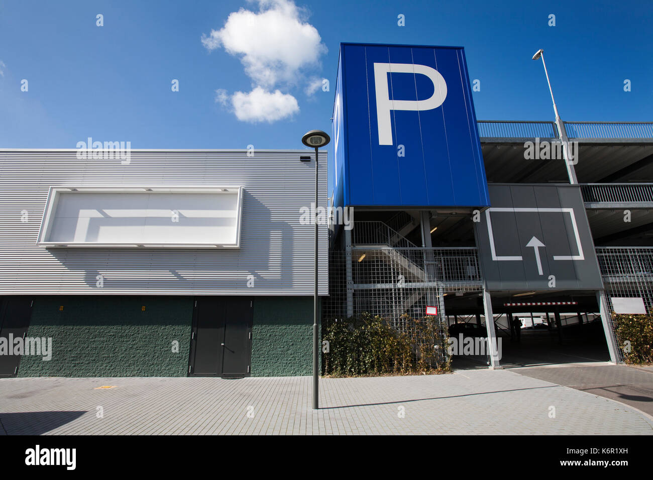 Blank billboard on a parking garage in Gouda. It's a public building with the entrance at the right side. A huge blue parking sign with a white P - Stock Image