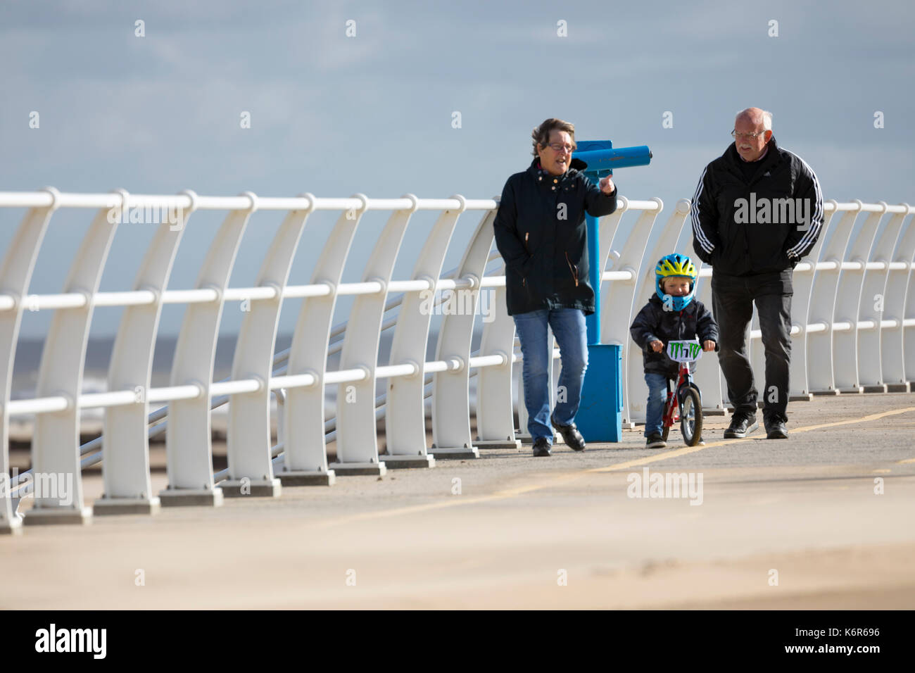North Wales, 13th September 2017.  UK Weather. The first named storm of season that brought 75mph gales to a central belt of the UK and North Wales now passing over North East of the UK. The Amber Warning for wind and rain is now reduce to yellow warning over North Wales as these people discovered along the promenade in Rhyl this morning, Denbighshire, Wales © DGDImages/Alamy Live News - Stock Image