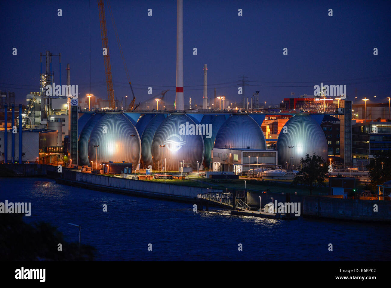 GERMANY, Hamburg, river Elbe,  illuminated biogas plant at treatment plant of Hamburg water , sludge is fermented to process Biogas / DEUTSCHLAND Hamburg, beleuchtetes Klaerwerk Koehlbrandhoeft von Hamburg Wasser, aus Klaerschlamm wird in einer Biogasanlage Biogas gewonnen und ins Gasnetz eingespeist - Stock Image
