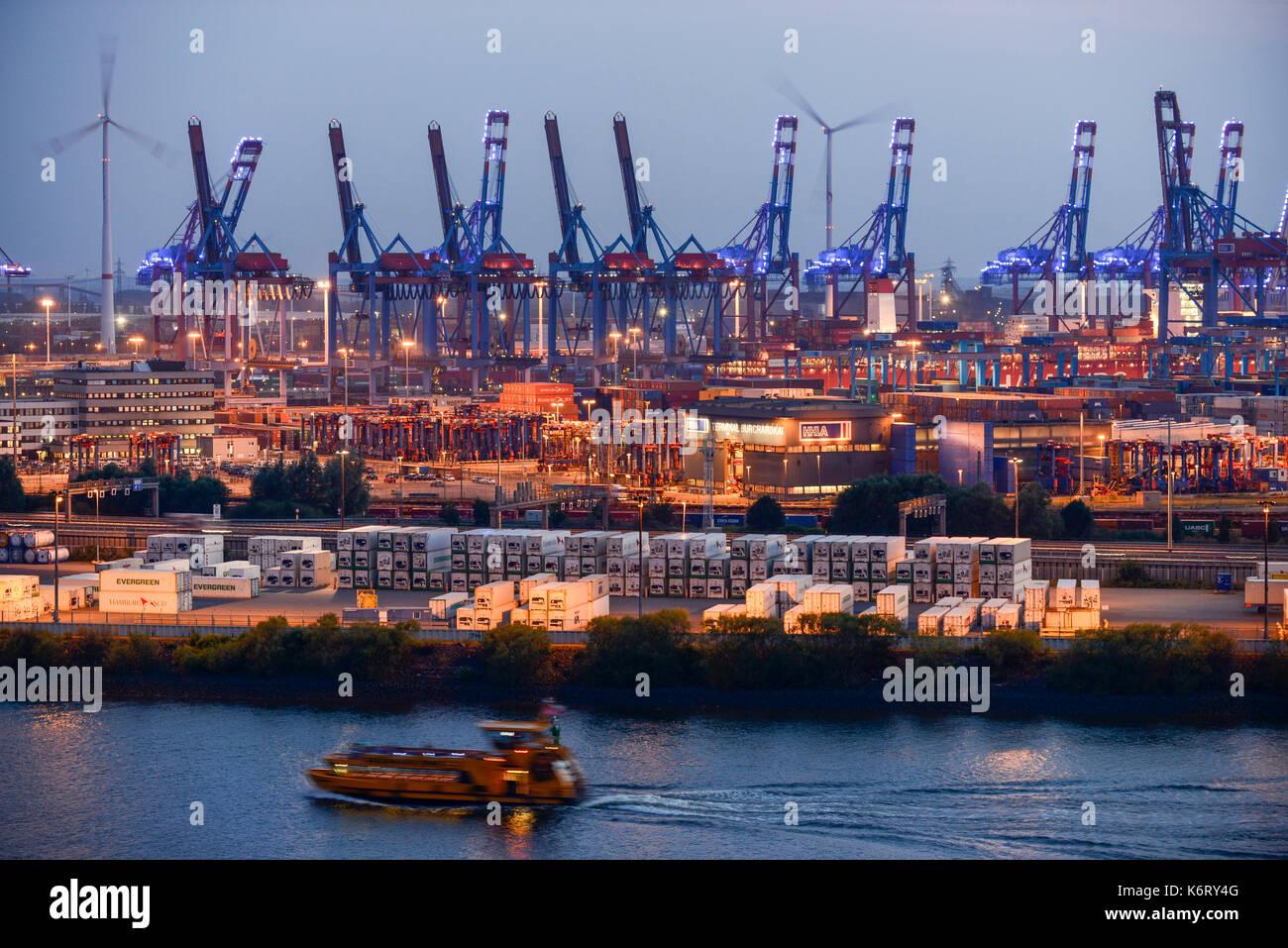 GERMANY Hamburg, light installation  blue port, HHLA container terminal and Nordex wind turbine in harbour / DEUTSCHLAND Hamburg, blue port Lichtinstallation im Hamburger Hafen von Michael Batz, Suederelbe, HHLA und Eurogate Containerterminal mit Nordex Windkraftanlagen - Stock Image