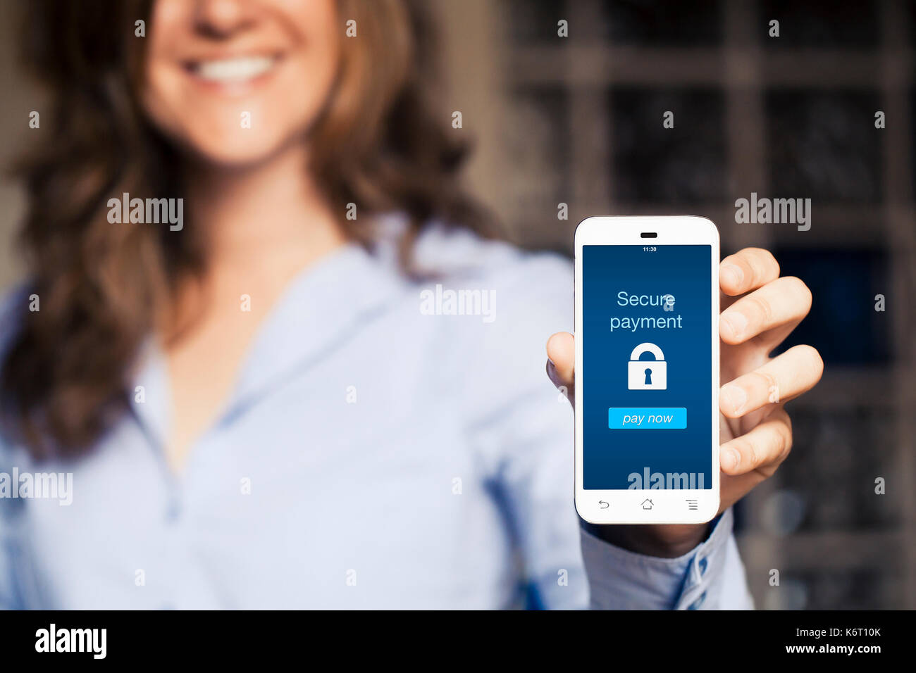 Secure payment notification in a mobile phone screen. Woman using a smartphone with online banking app in the screen. - Stock Image
