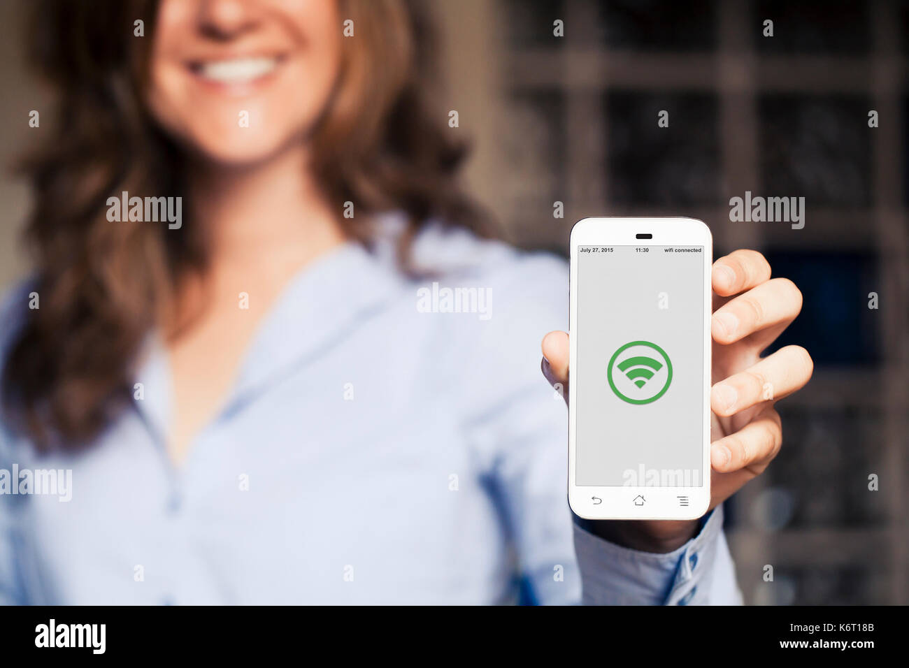 Smiling woman showing a mobile phone screen with a green wifi icon in the screen. Stock Photo
