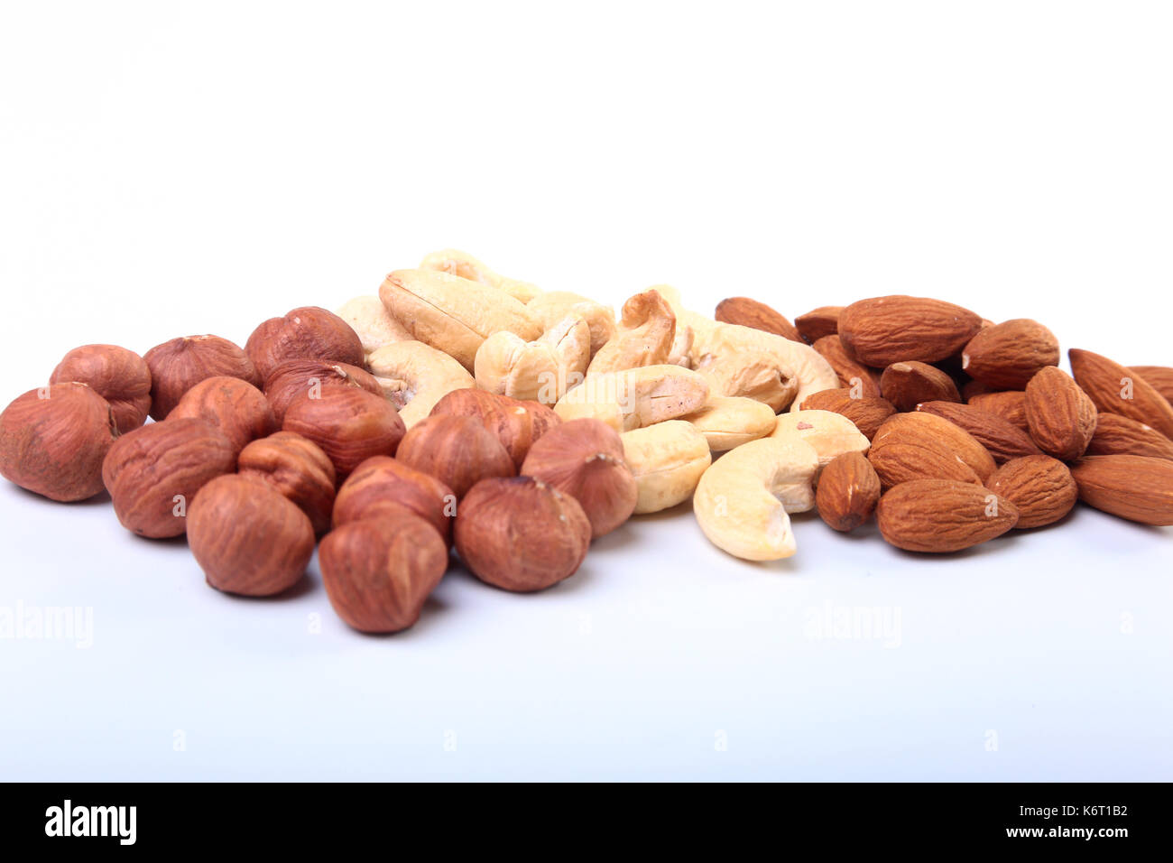 Mixed nuts from hazelnuts, almonds, cashews isolated on white background. Selective focus. Stock Photo