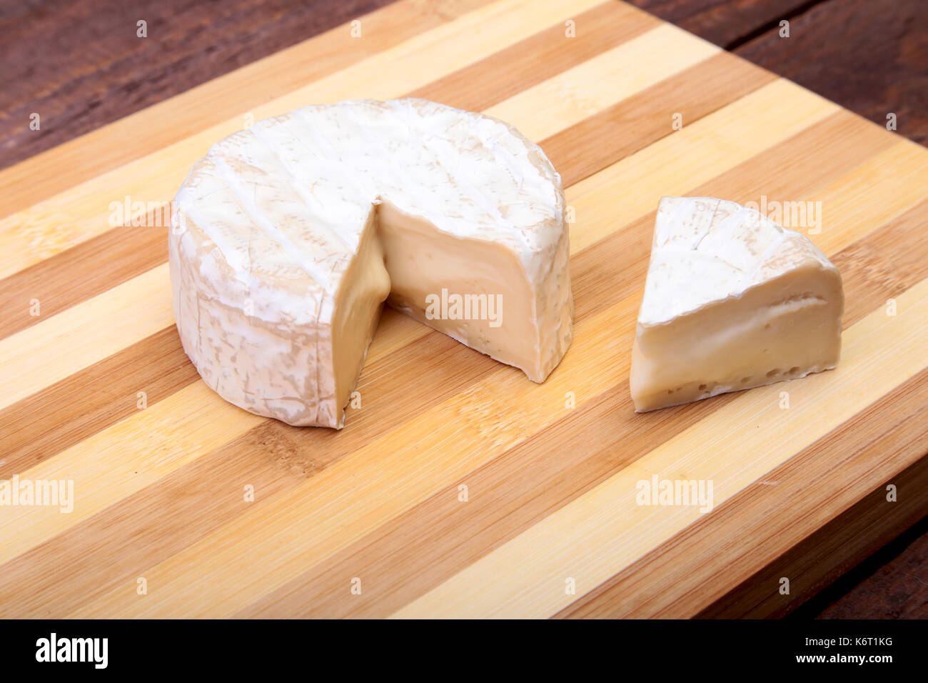 Cheese with white mold. Camembert or brie type on wood table. Healthy breakfast. - Stock Image
