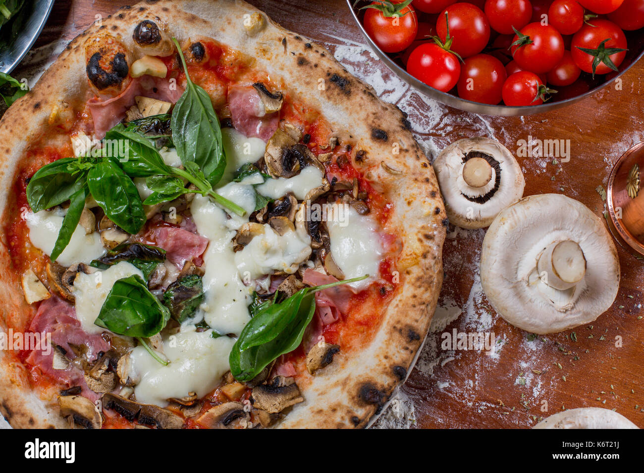 Pizza capricciosa with artichoke, ham and mushroom on wood background - Stock Image