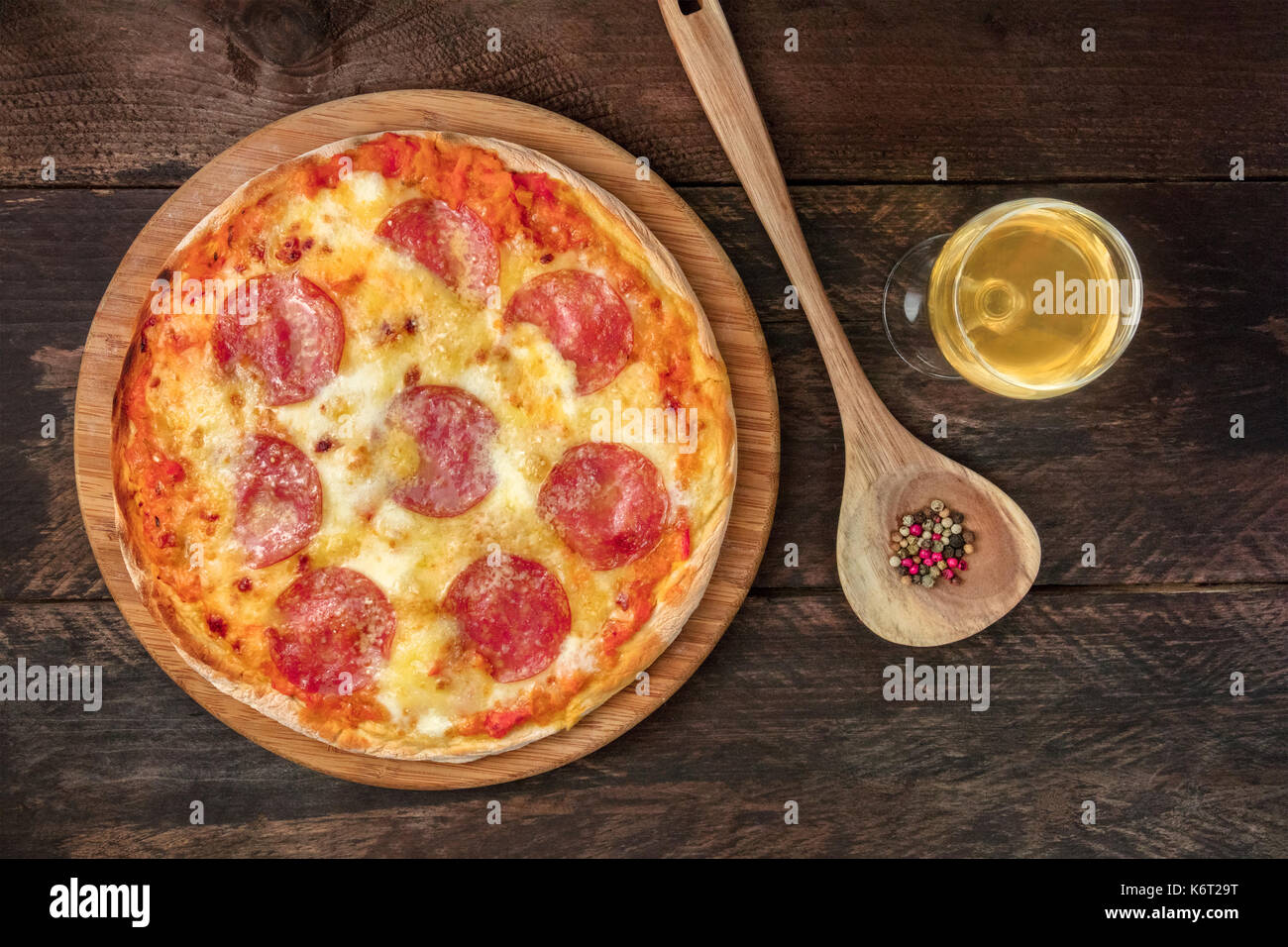 Pepperoni pizza with white wine, peppercorns, and copyspace - Stock Image