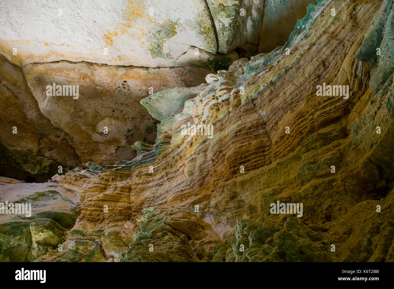 Cliff side cave, formed by sea erosion, containing evidence of sedimentation with different sediment layers having different colours. Cliffs in Malta - Stock Image