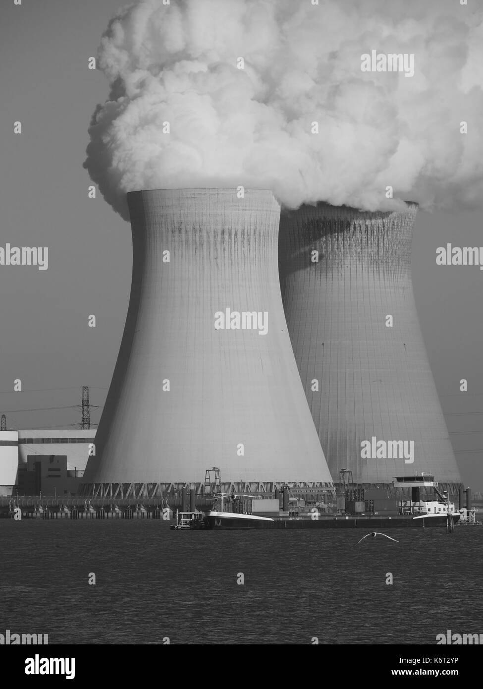 A monochrome photograph of two cooling towers of a nuclear power plant with a passing boat in the foreground. - Stock Image