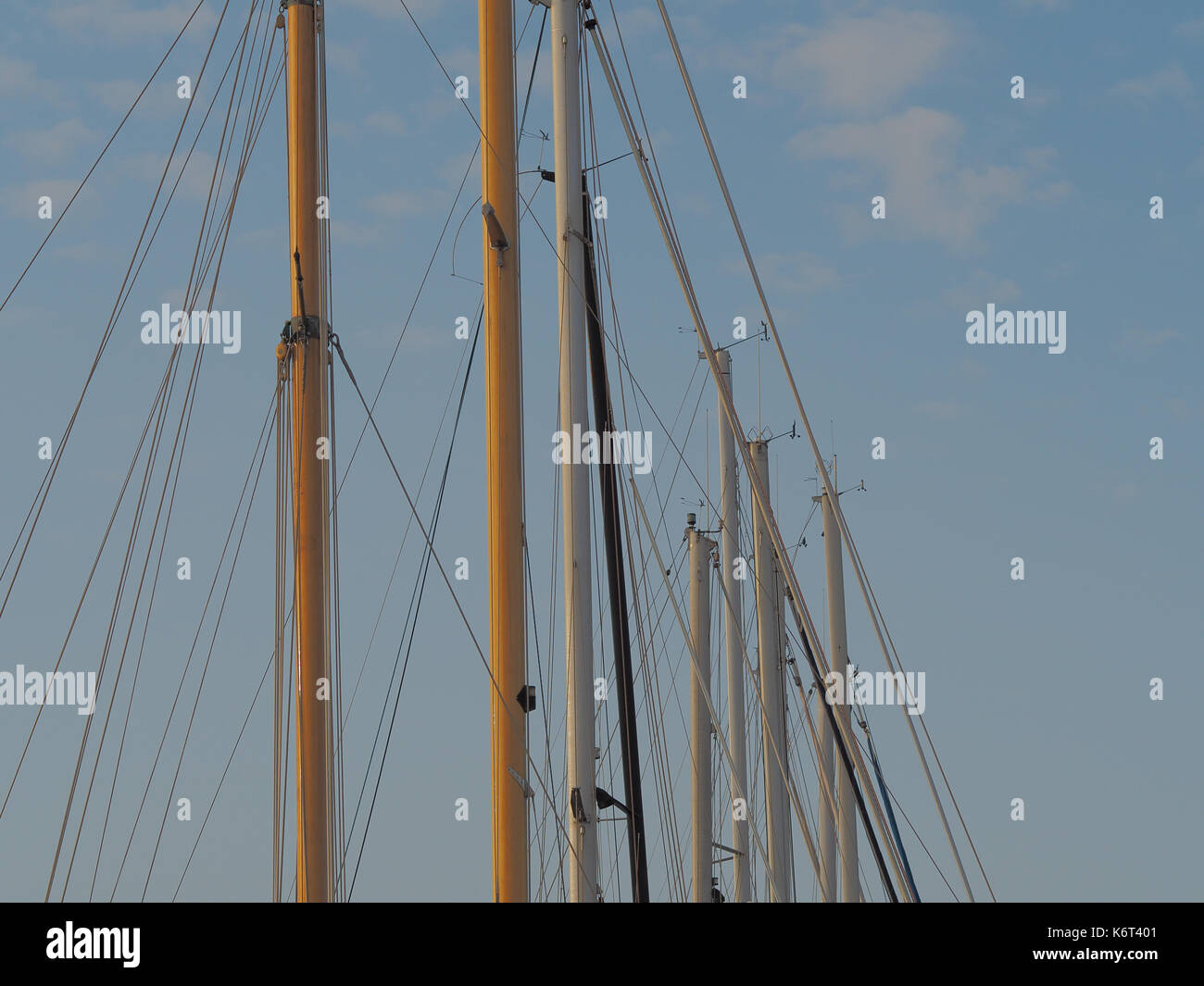 A series of masts of multiple sailboats. - Stock Image