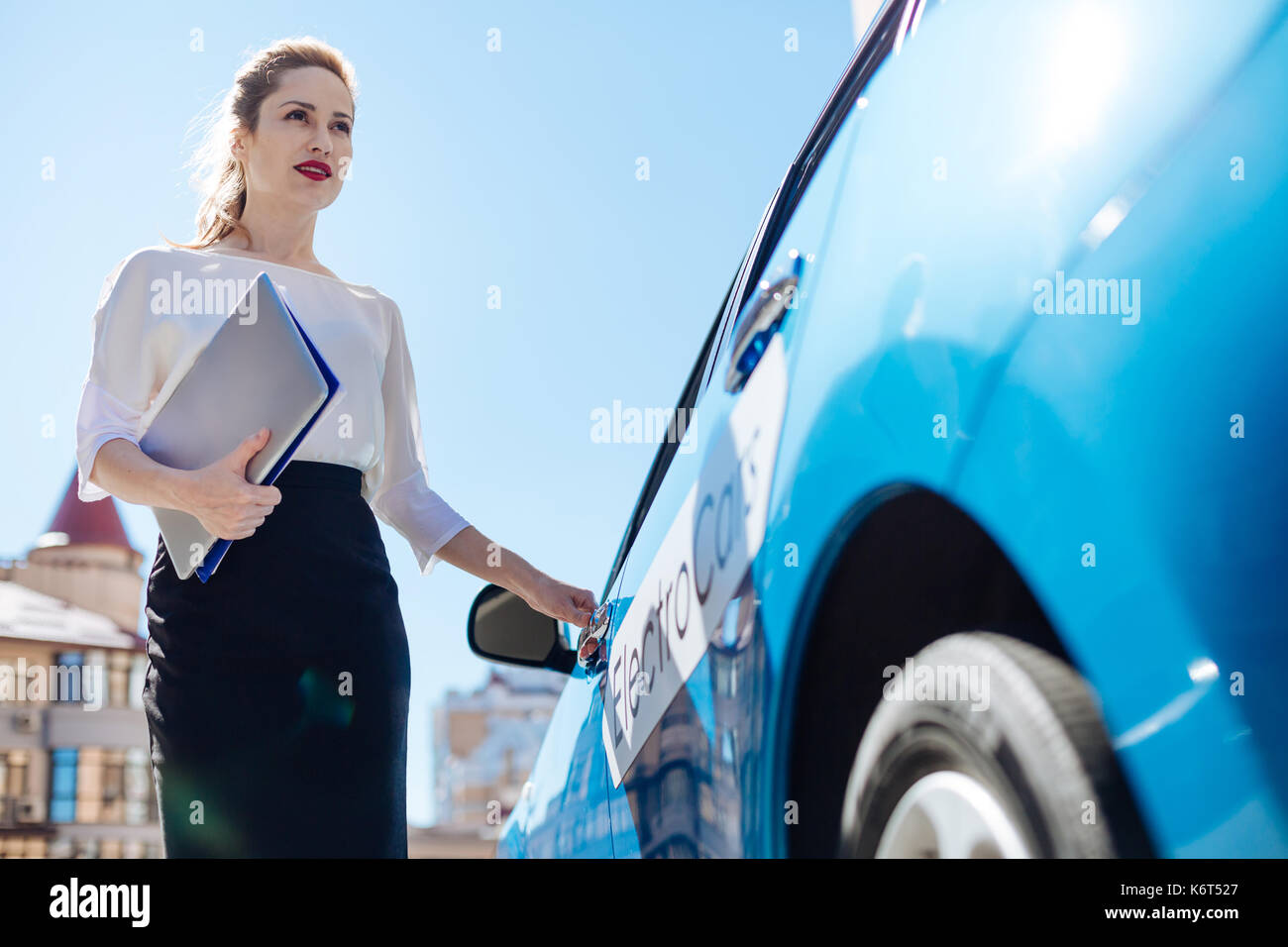 Attractive confident businesswoman opening her car - Stock Image
