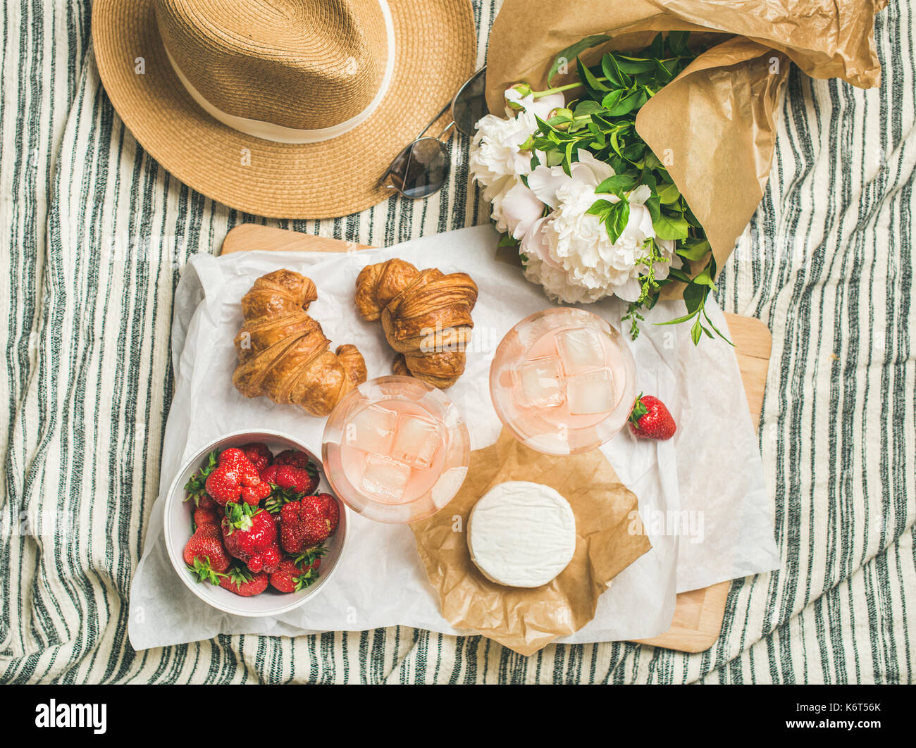 Flat-lay of glasses of rose wine, strawberries, croissants, brie cheese - Stock Image