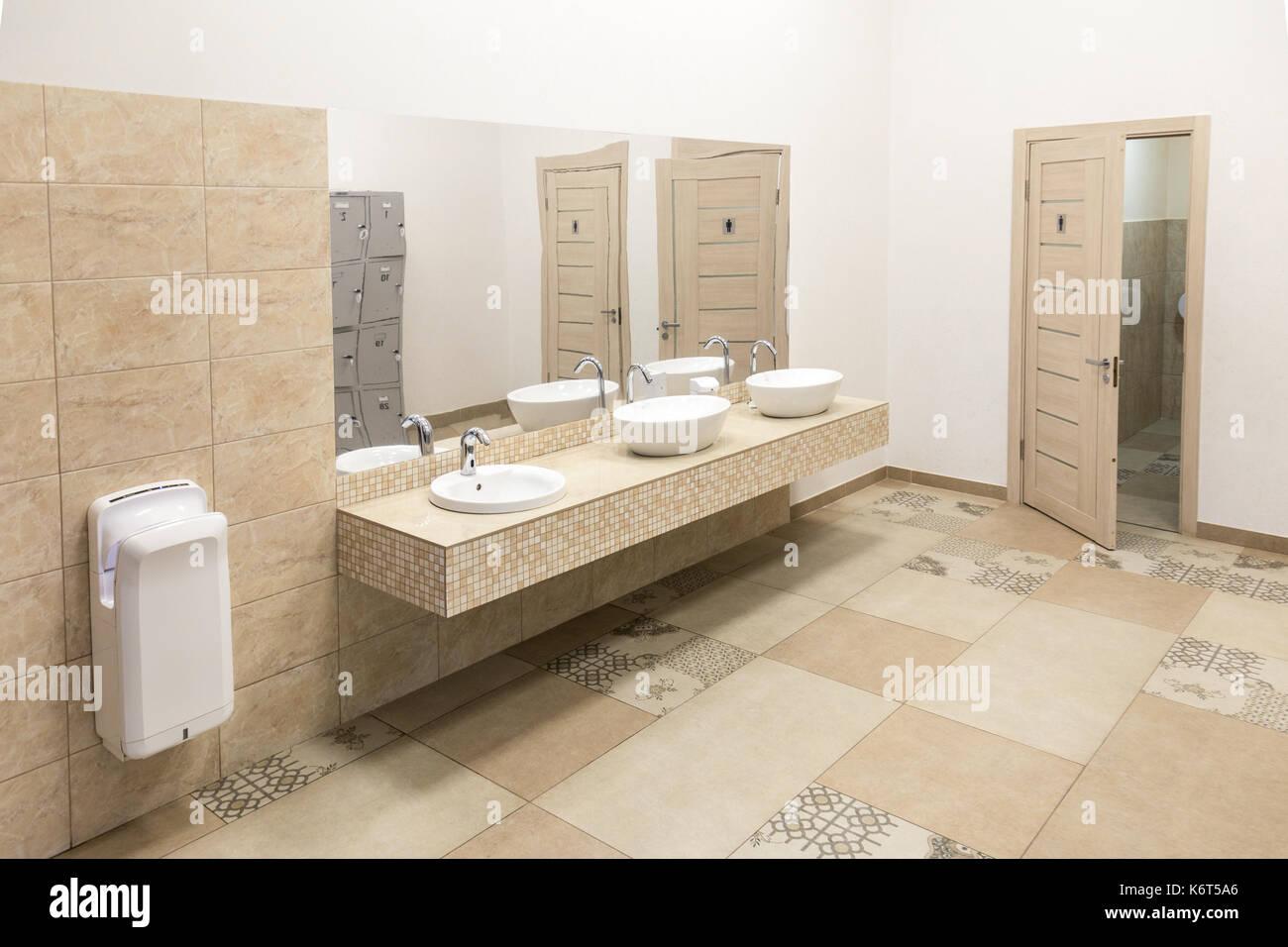 Public toilet wit big mirror, handwashers, dryer and wc doors Stock ...