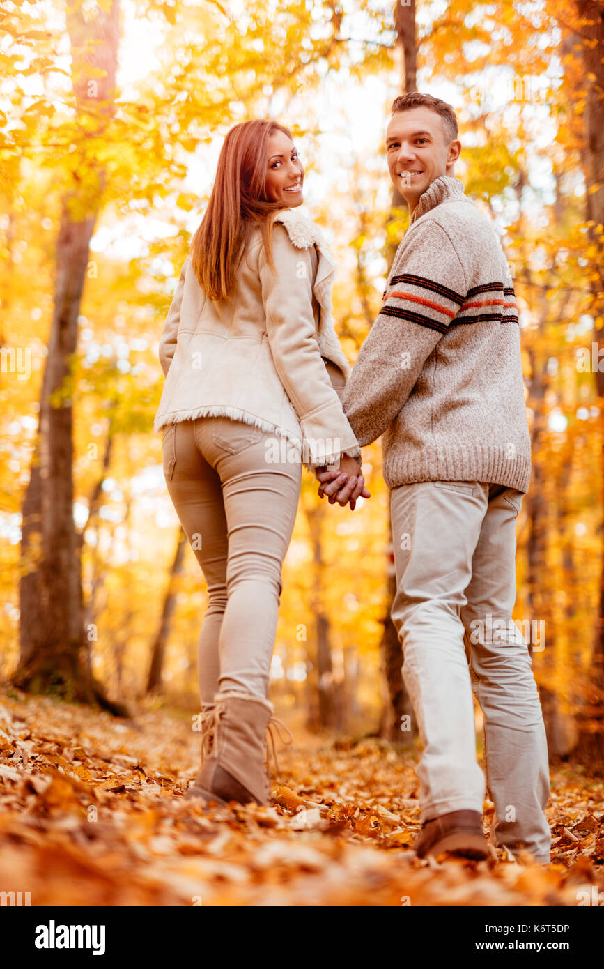 Beautiful smiling couple walking in sunny forest in autumn colors. Looking at camera, rear vew. Stock Photo
