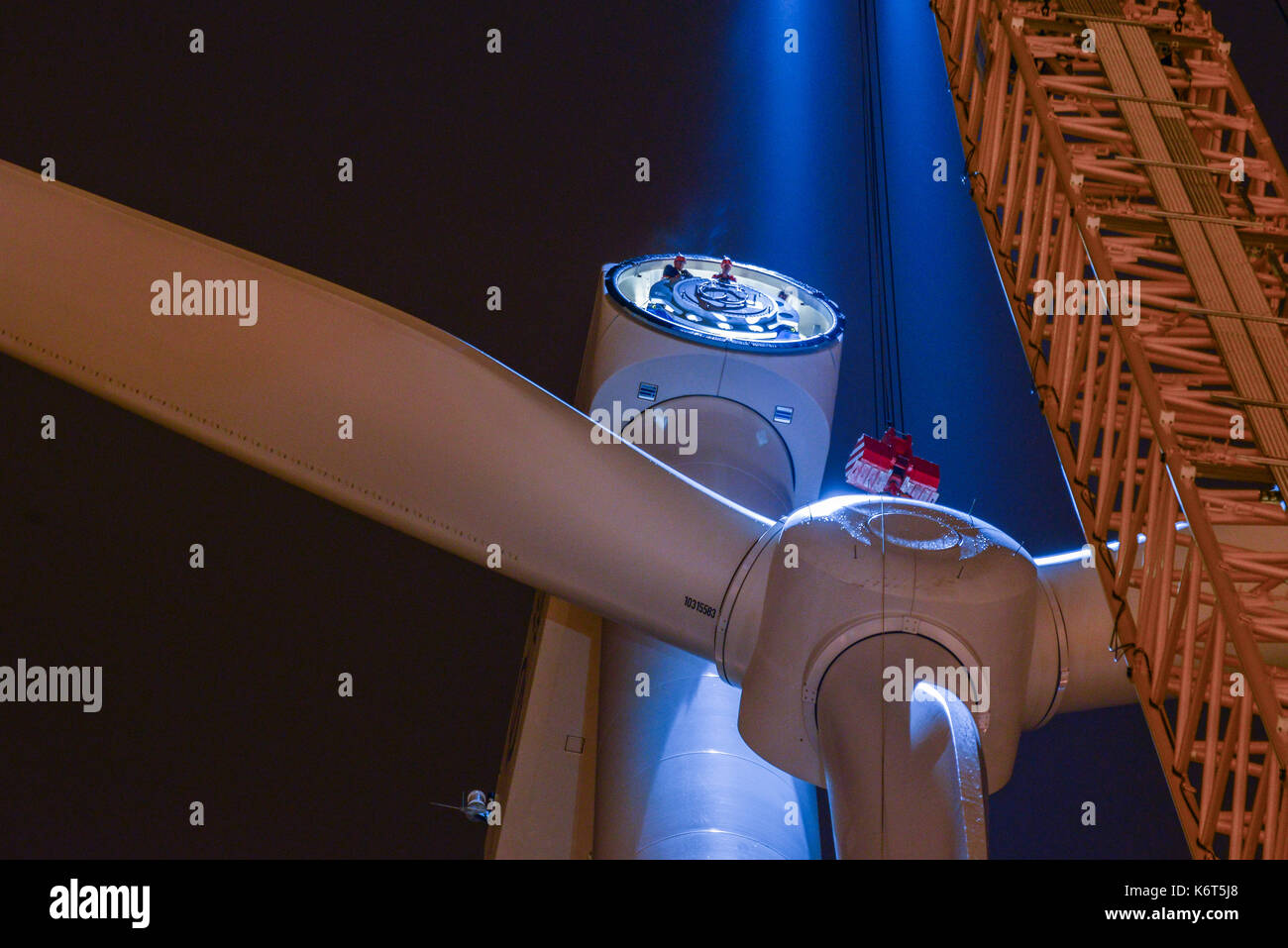 GERMANY Hamburg, construction of new Nordex wind turbine at water treatment plant of Hamburg Wasser art night , montage of rotor star with blades with crane - Stock Image