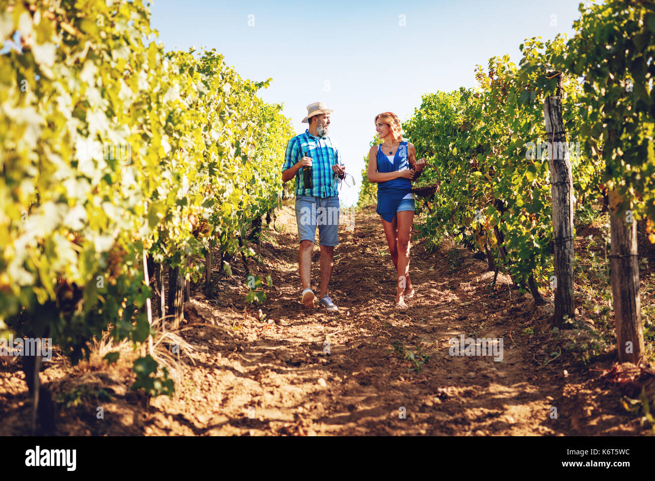 Beautiful smiling couple walking through a vineyard and tasting wine. - Stock Image