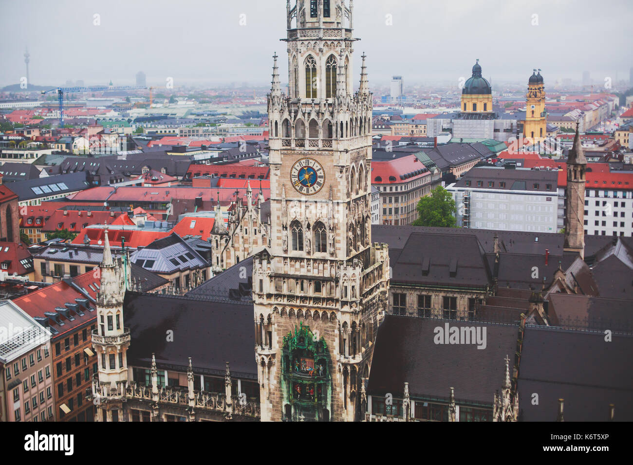 Beautiful super wide-angle sunny aerial view of Munich, Bayern, Bavaria, Germany with skyline and scenery beyond the city, seen from the observation d - Stock Image