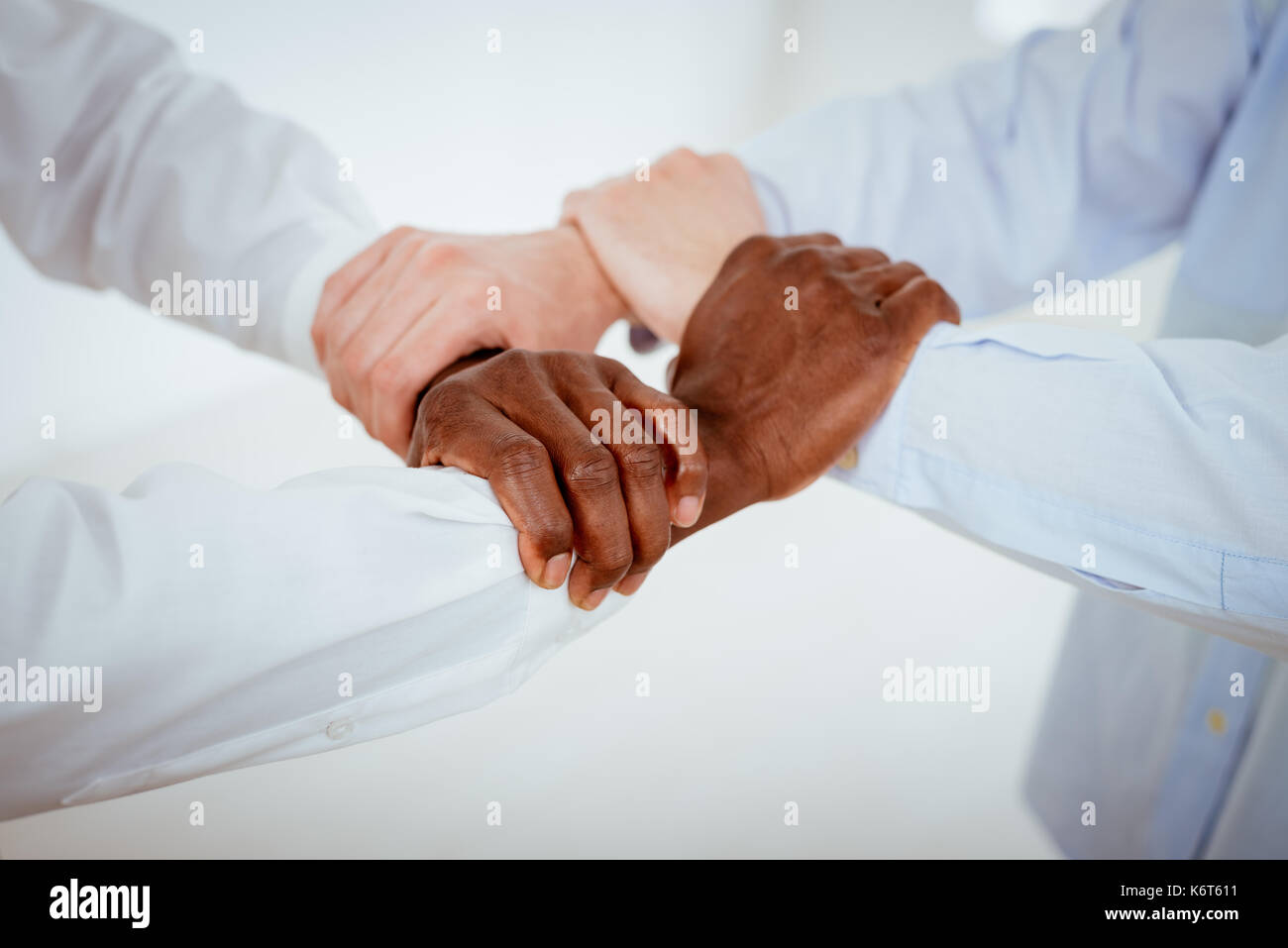 Close up of a four black and white hands holding together tightly stock