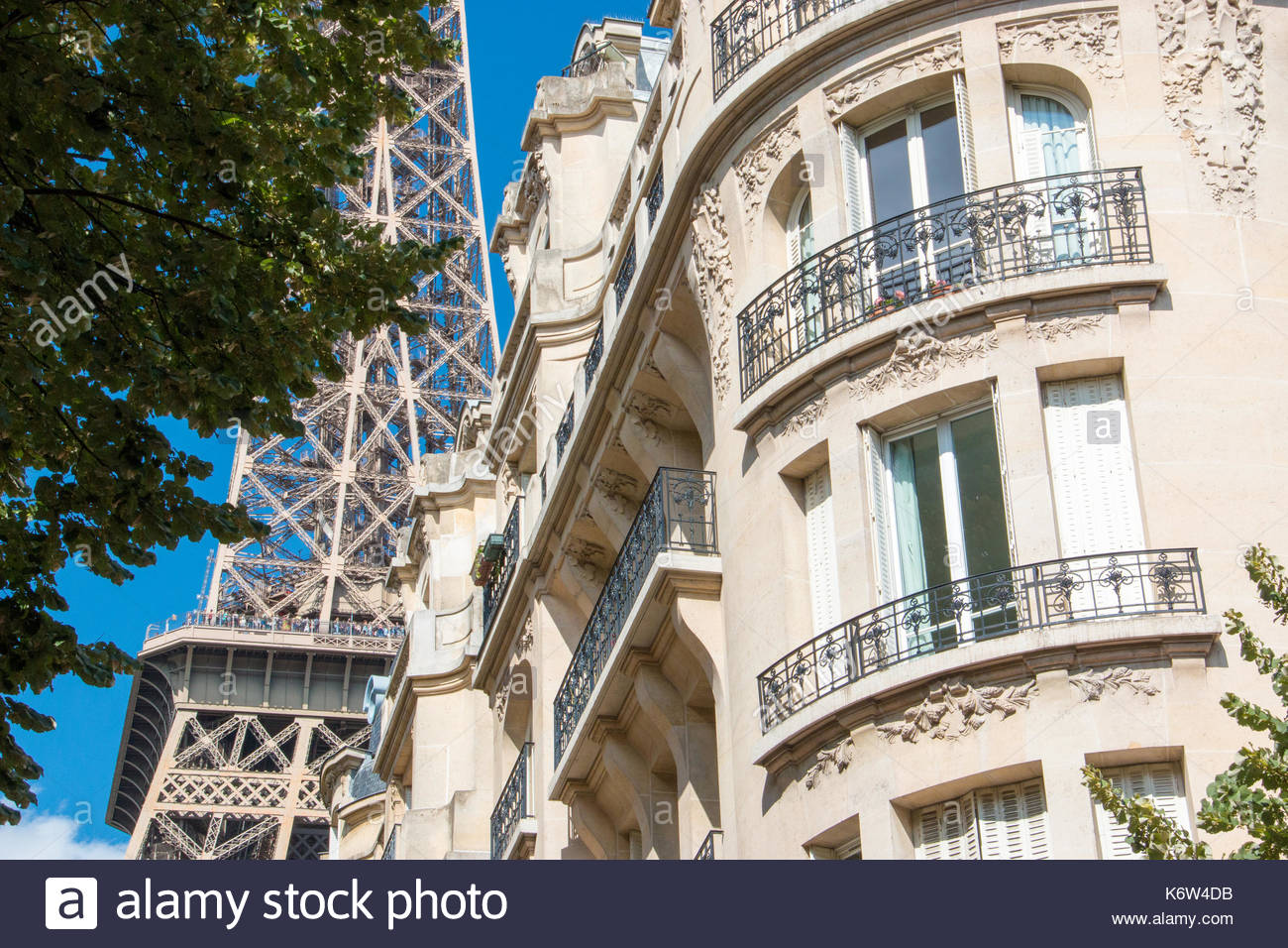 Eiffel tower, behind a Haussmann style building in Paris. - Stock Image