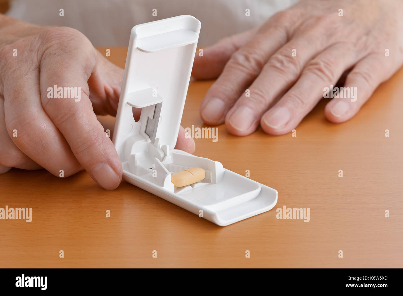 Two hands on a wooden tabletop holding a white plastic pill or tablet cutter with one big orange tablet pill inside, Stock Photo