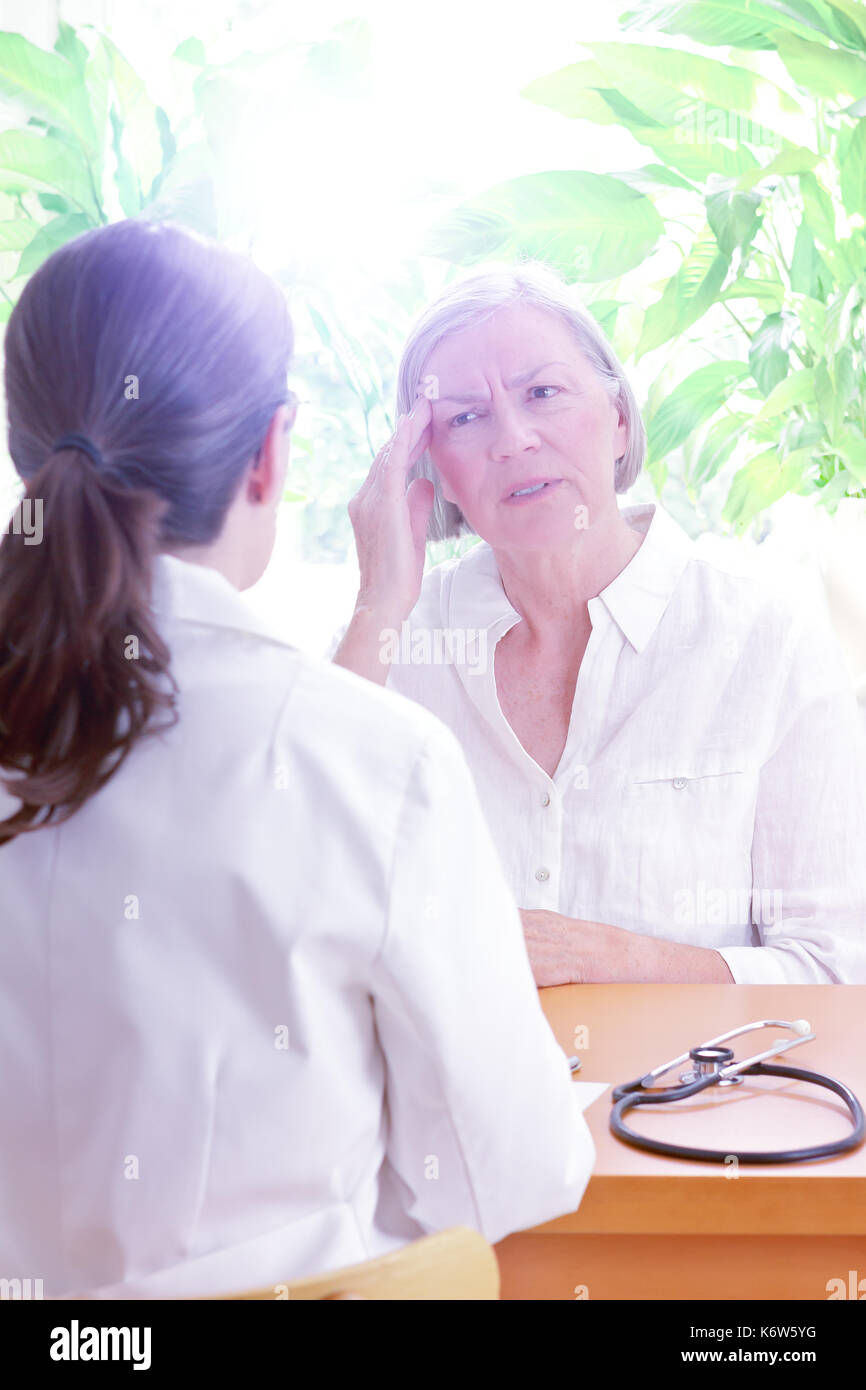 Female doctor with her senior patient with sleeping trouble, suffering of splitting headache or migraine, copy space Stock Photo