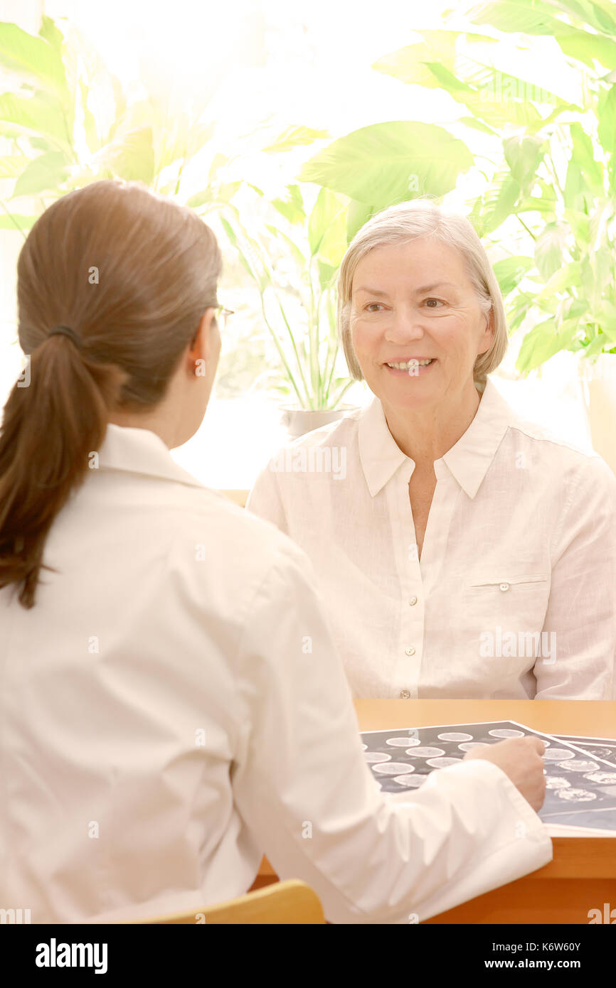 Female middle aged doctor showing her senior patient an ct scan of her head, sunny, light atmosphere Stock Photo