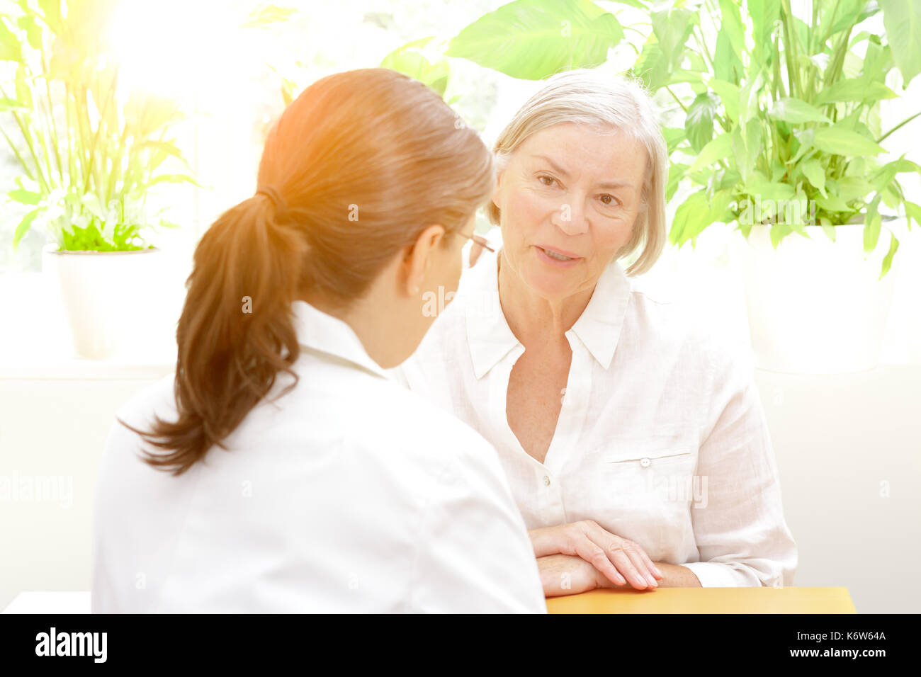 Senior patient discussing something in confidence with her female doctor of geriatrics on a sunny afternoon, friendly Stock Photo