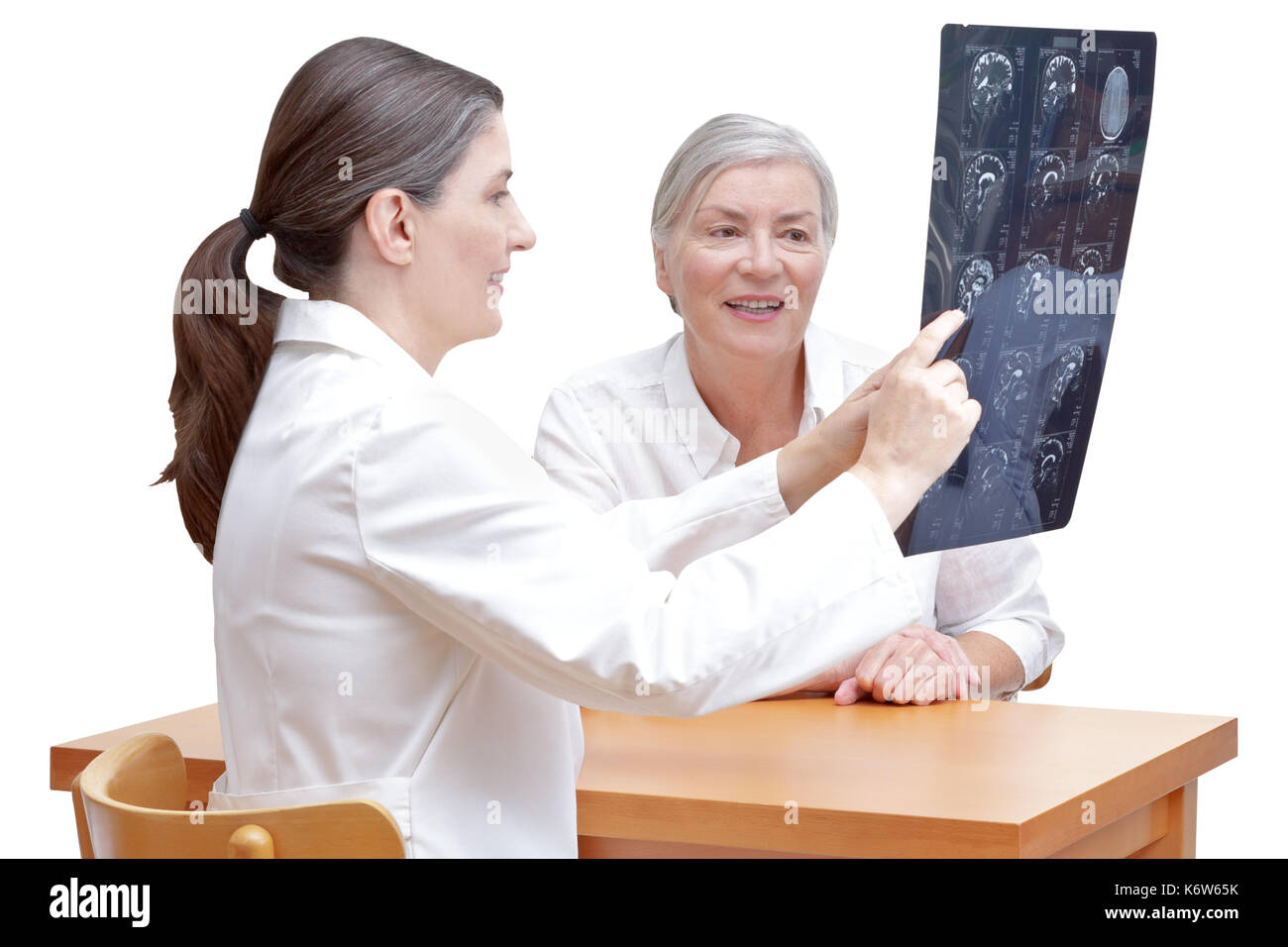 Female middle aged doctor showing her senior patient an mri of her head, isolated on white background Stock Photo