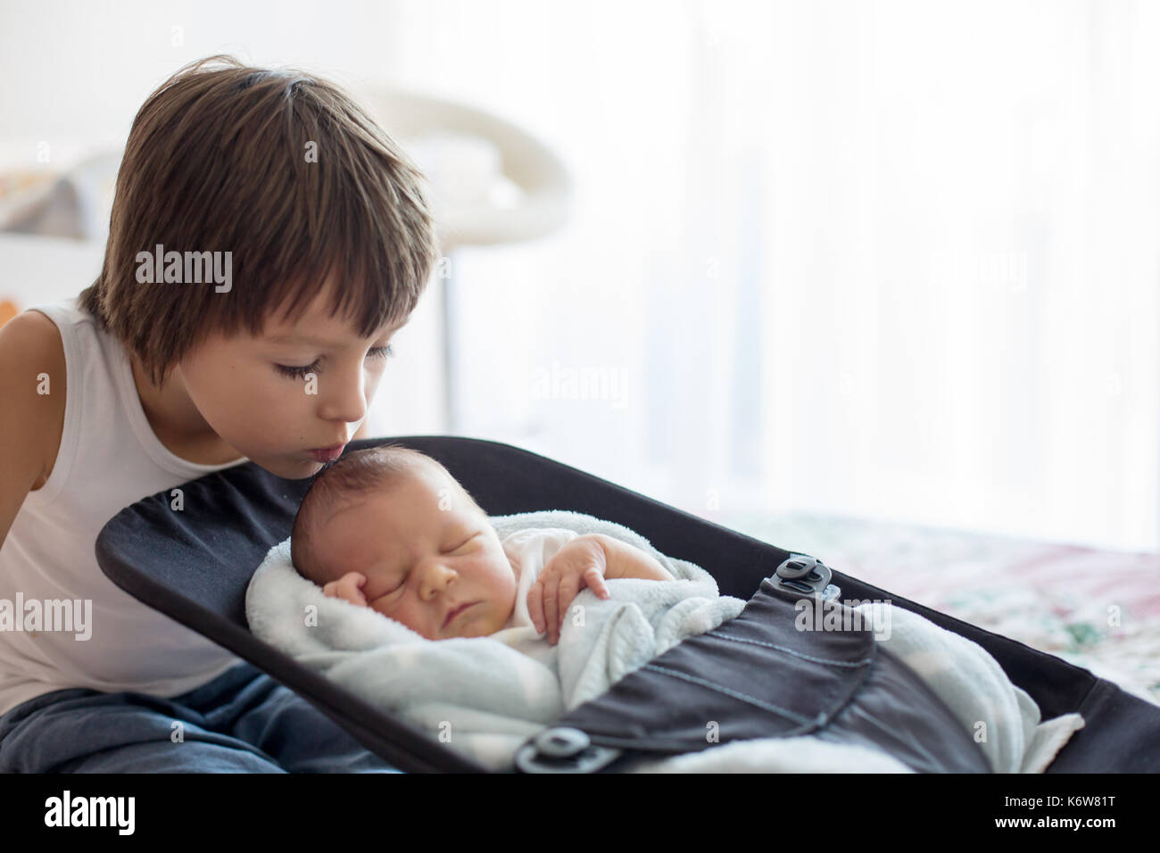 Beautiful boy, hugging with tenderness and care his newborn baby brother at home. Family love happiness concept - Stock Image